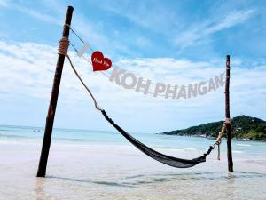 A picture of a hammock floating above shallow, crystal clear waters of a tropical island